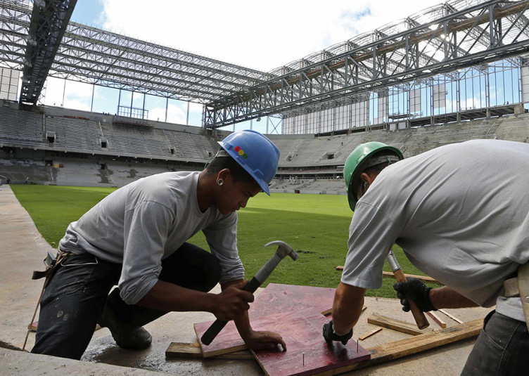 Workers are pictured inside the Arena da Baixada soccer stadium as it is being built to host matches of the 2014 World Cup in Curitiba